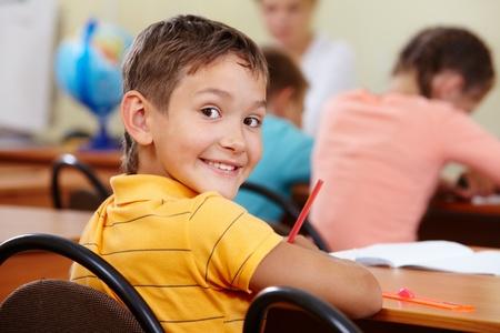 niños en la escuela: Retrato de muchacho inteligente en el lugar de trabajo con sus compañeros en el fondo