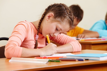 junior education: Portrait of lovely girl writing in copybook with schoolboys on background