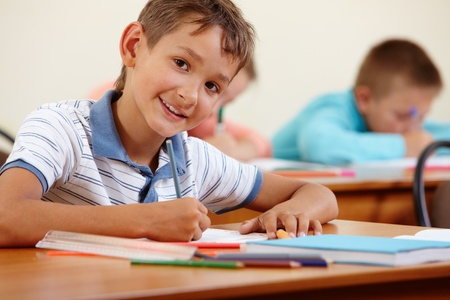 school desk: Portrait of smart lad at workplace with classmates on background