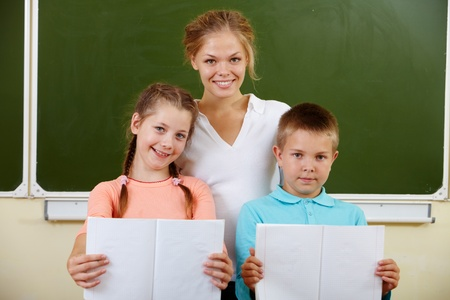 Portrait of cute schoolchildren showing their copybooks with teacher near by photo