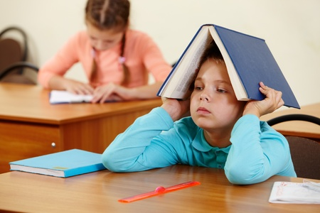 place to learn: Cute schoolboy keeping open book on head in classroom Stock Photo