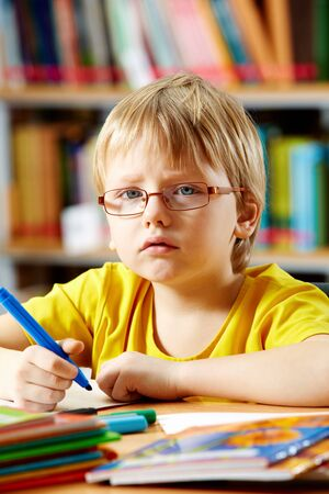 Portrait of clever boy drawing with highlighters  photo