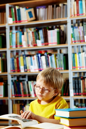 literary: Portrait of cute schoolkid reading book in the library Stock Photo
