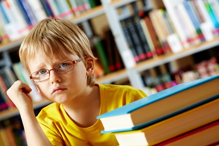 Portrait of clever boy thinking in library photo