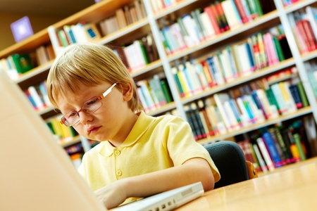 Portrait of serious schoolkid working with laptop in the library photo