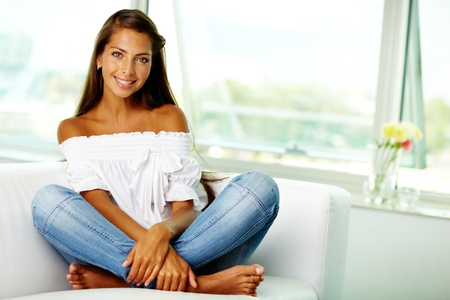 barefoot girls: Portrait of cute brunette sitting on sofa at home