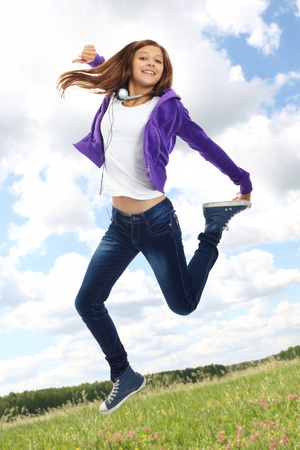 Cute girl in casual clothes jumping over green field photo