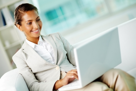 users: Portrait of smiling businesswoman with laptop in office Stock Photo