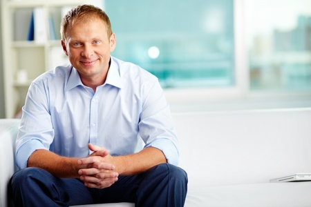 specialists: Portrait of confident man sitting in office Stock Photo