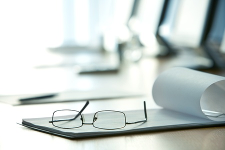 CONFERENCE TABLE: Image of workplace with paper and eyeglasses Stock Photo