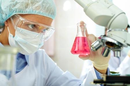 Chemicus houdt steekproef van vloeistof in het laboratorium