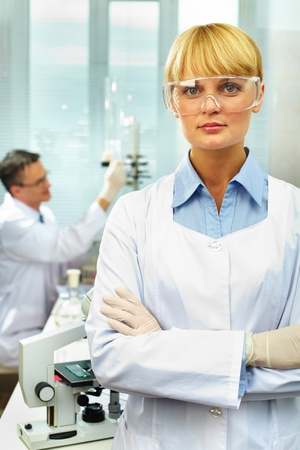 Portrait of a pretty scientist looking at camera against her working colleague photo