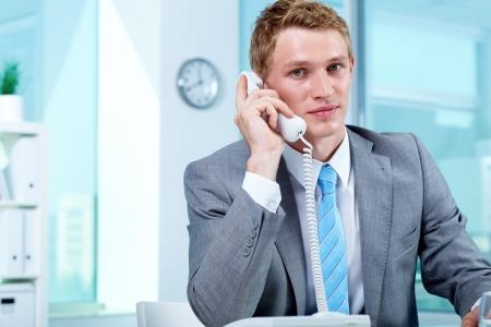 agente comercial: Retrato de un hombre de negocios hablando por teléfono en la Oficina Foto de archivo