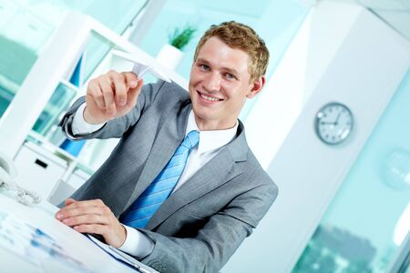 Portrait of a successful employer at workplace holding paper plane photo