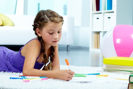 junior education: Portrait of lovely girl drawing with colorful pencils Stock Photo