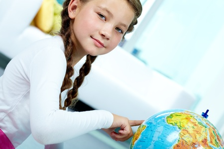 Portrait of cute child with globe looking at camera   Stock Photo - 10378455