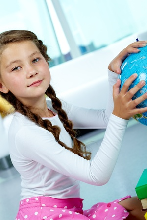 pigtails: Portrait of cute child with globe looking at camera
