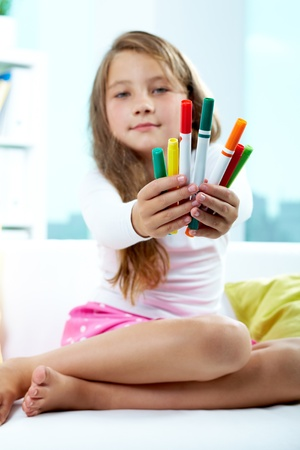 Portrait of lovely girl giving colorful pencils photo