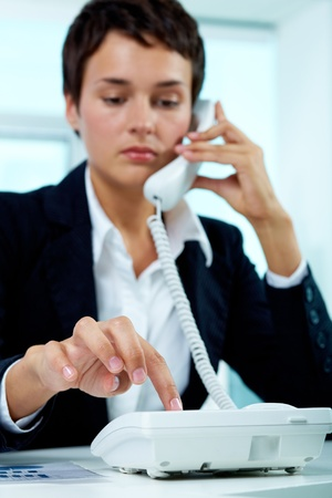 principal: Photo of smart businesswoman pressing phone buttons in office