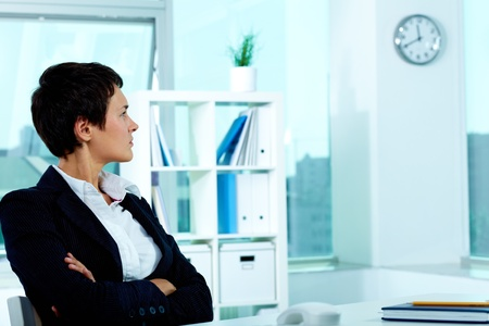 Photo of smart businesswoman sitting in office and looking at clock photo