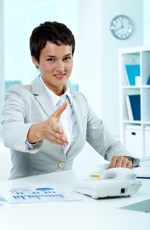 principal: Portrait of pretty employer at workplace giving you hand for handshake Stock Photo