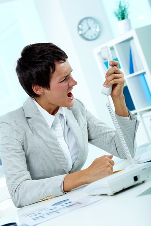 Image of annoyed boss losing her temper and screaming into phone receiver Stock Photo - 10378458
