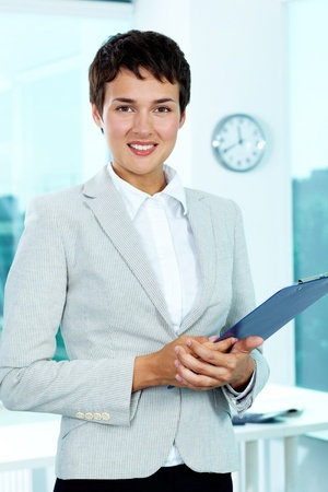 principal: Photo of smart businesswoman with clipboard looking at camera