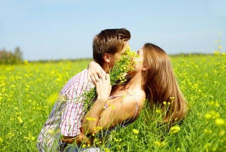 novios besandose: Retrato de la joven pareja rom�ntica abrazando mutuamente en el campo de flores