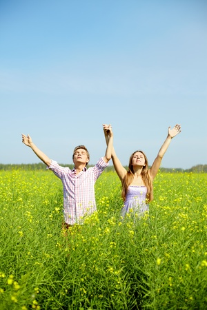 Portrait of young couple with raised arms standing in flower field Stock Photo