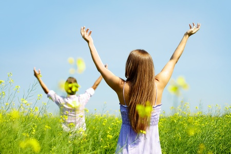 surrender: Backs of young couple with raised arms standing in flower field
