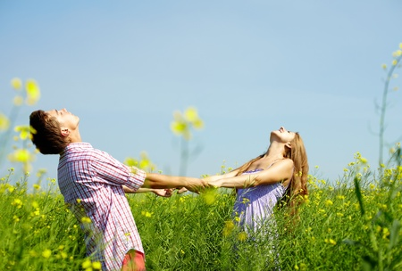 raised arms: Portrait of happy young couple with raised arms standing in flower field Stock Photo