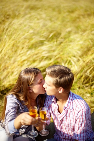 Portrait of happy young couple with flutes kissing outside