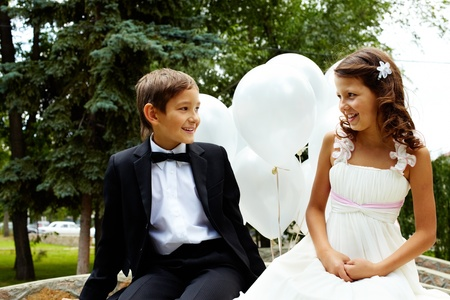 Portrait of children bride and groom with balloons chatting in park  photo