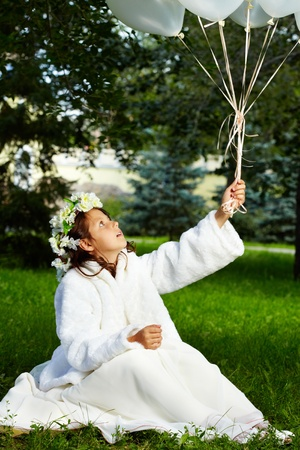 amused: Portrait of amused girl bride with balloons in park