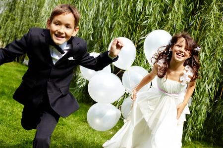 Portrait de rire mariée et le marié les enfants avec des ballons en cours d'exécution dans le parc