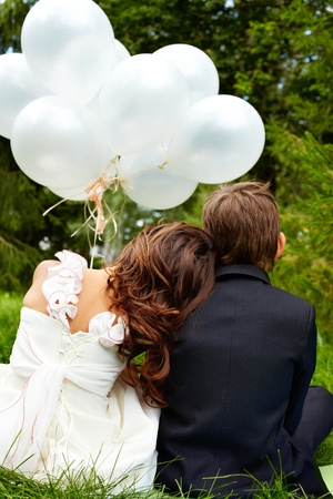 Backs of children bride and groom with balloons sitting in park  photo