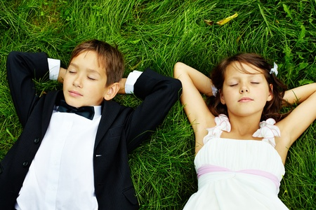 Portrait of calm children bride and groom lying on green grass  photo