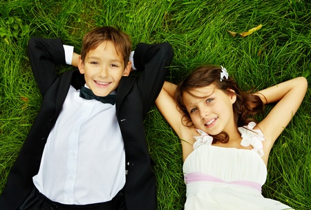 tuxedo man: Portrait of smiling children bride and groom lying on green grass and looking at camera Stock Photo