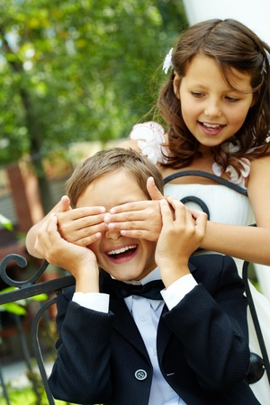 Portrait of cute girl bride shutting eyes of her laughing groom photo