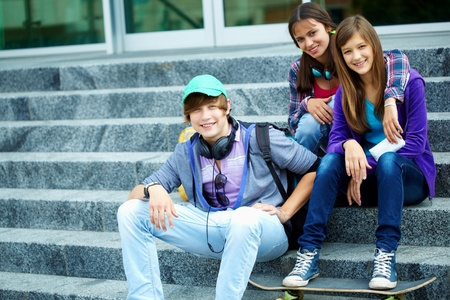 youthful: Portrait of happy teens on stairs looking at camera Stock Photo