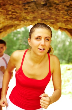Image of pretty young girl running in park photo