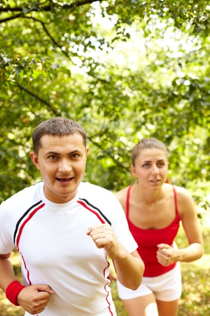 Image of happy young sportsman running with his girlfriend behind photo