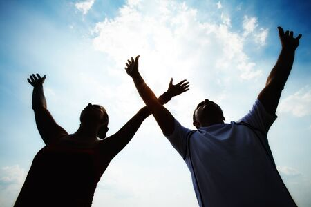 race relations: Silhouettes of sporty couple raising arms against cloudy sky