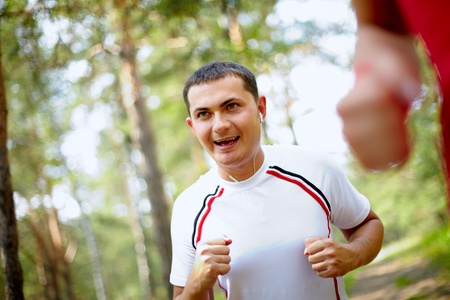 Image of happy young sportsman with earphones running in park Stock Photo - 10446058