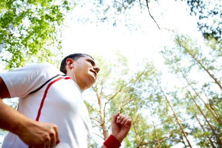 Image of young sportsman with earphones running in park photo
