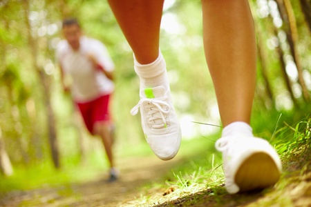sock: Image of human feet in sportshoes running down grass Stock Photo