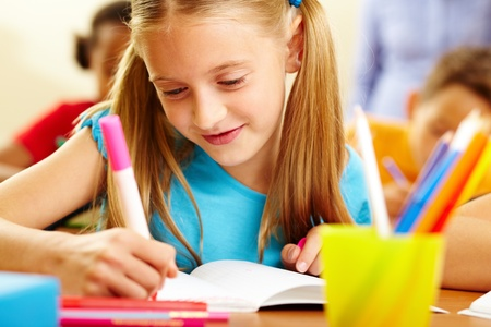 Portrait of lovely girl drawing in copybook at lesson Stock Photo - 10446080