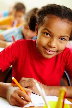 ni�os en la escuela: Retrato de ni�a encantadora en lecci�n de dibujo con l�pices de colores