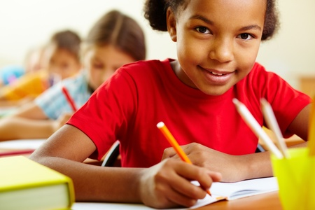 child learning: Portrait of cute girl drawing with crayons at lesson