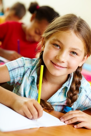 lifestyle looking lovely: Portrait of lovely girl drawing in copybook at lesson